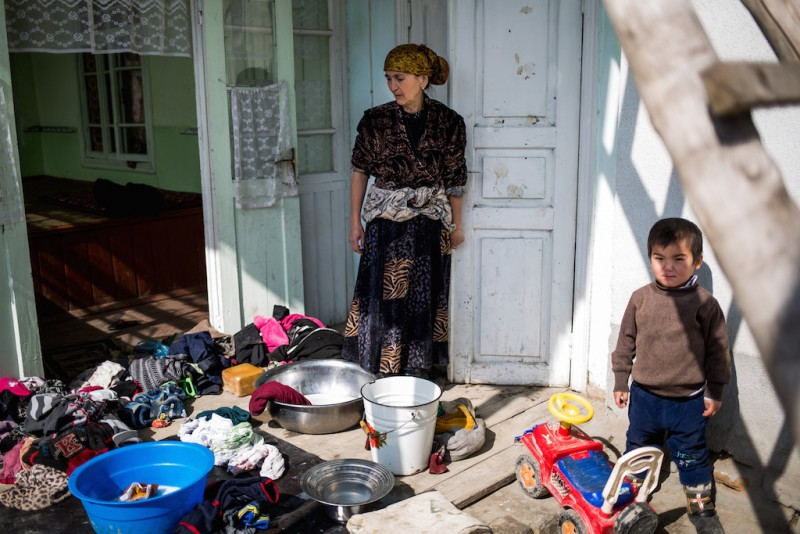 "Manzura, 55 years old, takes care of her five grandchildren. Their parents divorced because of the husband's alcoholism, and their mother went to work in Russia. Manzura receives a monthly pension of 3000 Kyrgyz soms (KGS). ""I tell them that their mom will come when she gets a vacation. They stopped asking about their father..."" Osh city, Osh oblast."