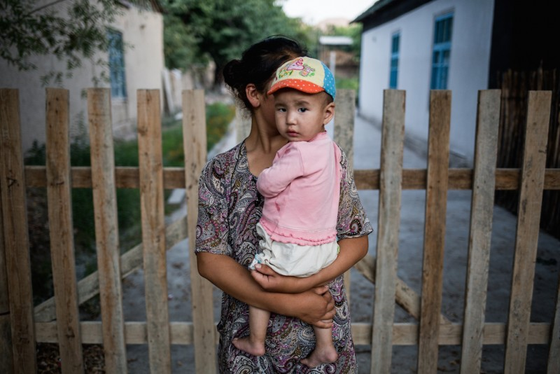 A mother with an infant. It is very difficult to meet a working-age youth in a Kyrgyzstani village since most have left for Russia to find work. Chek village, Batken oblast.