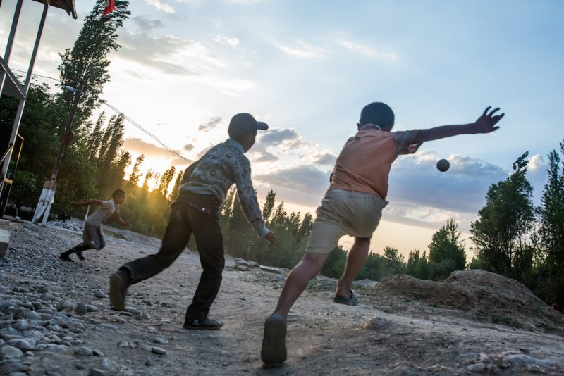 Children playing football in a yard. Students freshly graduated from the third to fifth class (ages eight to eleven years) are the most vulnerable to labor migration. Some children even begin planning their trip to Russia long before graduating. Isfana city, Batken oblast.