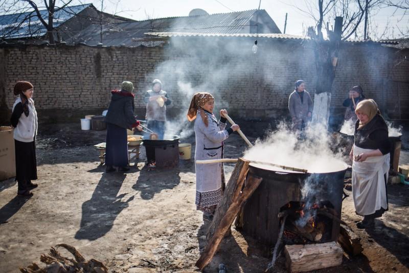 Women cooking Sumalyak, a traditional Springtime dish. Osh city, Osh oblast.