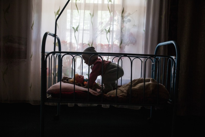 A one-year-old child left by her parents and raised by her grandmother. Her grandmother has made a crib by installing a lattice around a bed. Because she is unable to take care of her granddaughter regularly, the grandmother devised this contraption to make sure the child does not wander away when she is not present. Karabag village, Batken oblast.