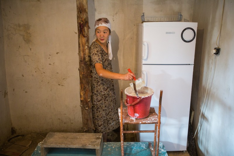 Savrinisa's daughter in law, 23 years old, repairs the house. All of the men in her family, including her husband, have gone to Russia to look for work. Djangijer village, Batken oblast.
