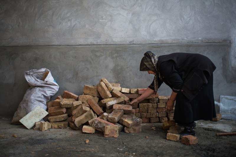 Mahfirat, a 60-year-old woman, collects bricks for the restoration of a destroyed house. Osh city, Osh oblast.