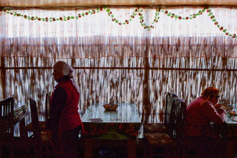 A choyhona, a traditional Uzbek teahouse, occupied by female Kyrgyz patrons. Normally, choyhonas are strictly male-only, but with so many men working in Russia, women have taken over the business. Aravan rayon, Osh oblast.