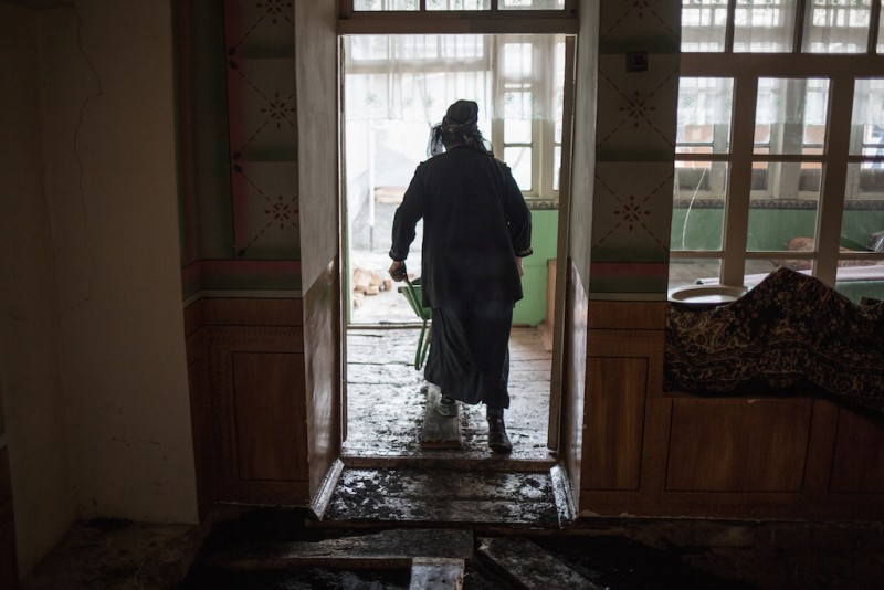 Mahfirat, 60 years old, renovates a house that suffered damage when its old foundations began to decay. All of Mahfirat's sons work in Russia, and her husband is ill and unable to perform hard labor. Osh city, Osh oblast.