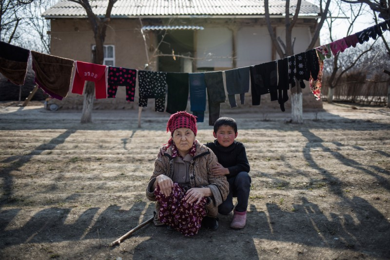 Sixty-year-old Ainysa and her grandson. All of her children work in Russia. Chek village, Batken oblast, Kyrgyzstan.