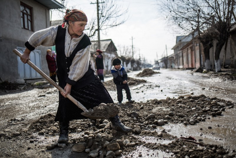 An elderly woman shovels mud from a destroyed road near her house. Osh city, Osh oblast.