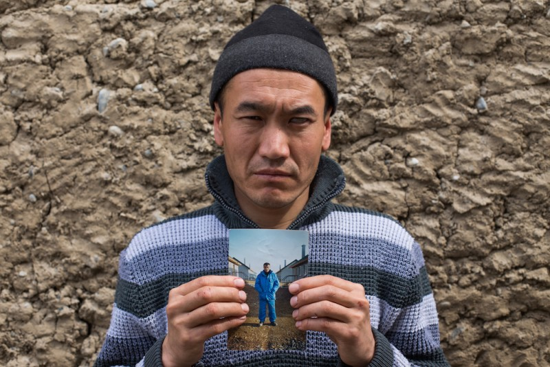 Asylbek, approximately 30 years old, holds a portrait of his brother who disappeared without a trace in early 2013, after thirteen years working in Russia. Their mother died in March 2013, and the family has no way of informing him. Batken city, Batken oblast.
