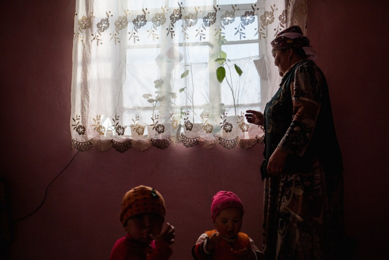 "Tologon, 63 years old, takes care of her two grandchildren, one six months old, the other twob years old. ""They often talk to their mother on the phone,"" she says. ""I say [to the children] that their mother will arrive in the summer. When summer comes, I say she will come in the winter, and she'll bring a lot of money..."" Aravan rayon, Osh oblast."