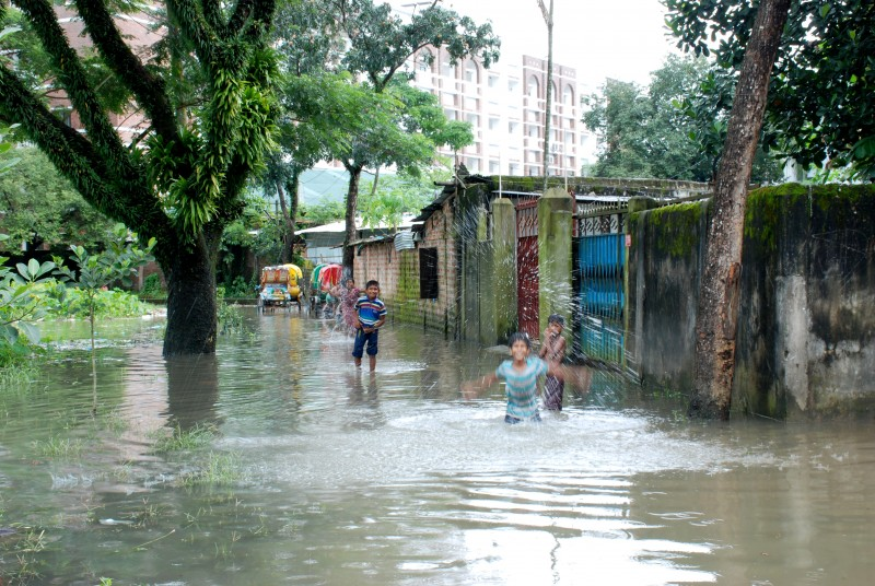 Children play in the dirty flood water in Sylhet city, Bangladesh, on September 2, 2015. Low-lying Bangladesh is perhaps the most vulnerable nation to the impacts of climate change. Photo by Md. Akhlas Uddin. Copyright Demotix