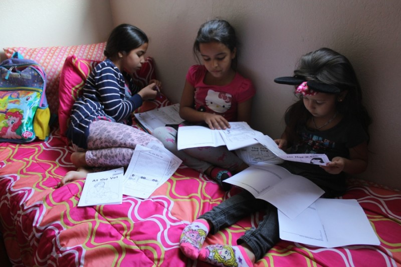 Arwa, left, Marwa, center, and Rawan, right, tackle their homework on a recent afternoon. The sisters arrive to Turlock, California, in February, after fleeing war in Syria.  Credit: Monica Campbell. Used with PRI's permission