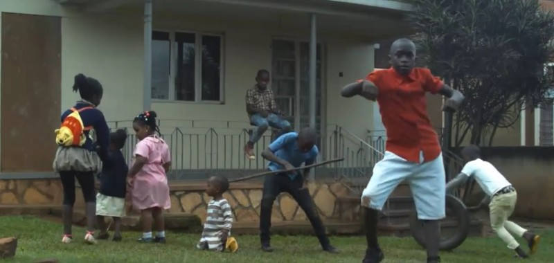 A screenshot of the Jambole video from YouTube showing Alex Ssempijja (in a red shirt) dancing.