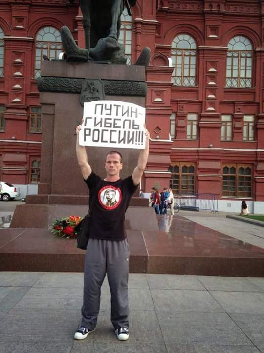 "Ildar Dadin at a single-person picket in Moscow in 2014. Poster reads: ""Putin is the downfall of Russia."""