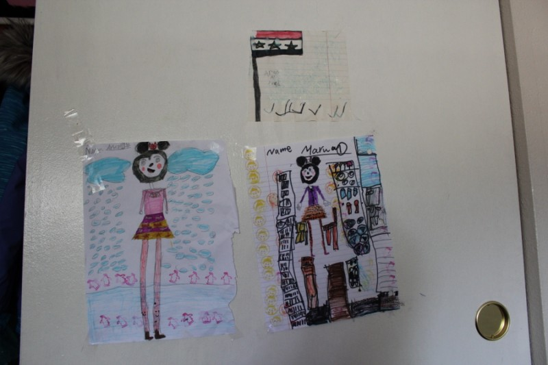 "The childrens' drawings in the bedroom of their new home in California. Arwa, 8, drew Syria's flag to ""not forget where I'm from.""  Credit: Monica Campbell. Used with PRI's permission"