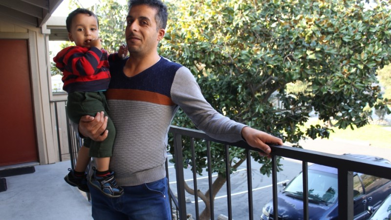 Gasem Al Hamad and his son, Mohamad, at their new home in Turlock, California. The Al Hamad family fled war in Syria and, after a three-year journey, arrived to the US as refugees.  Credit: Monica Campbell. Used with PRI's permission