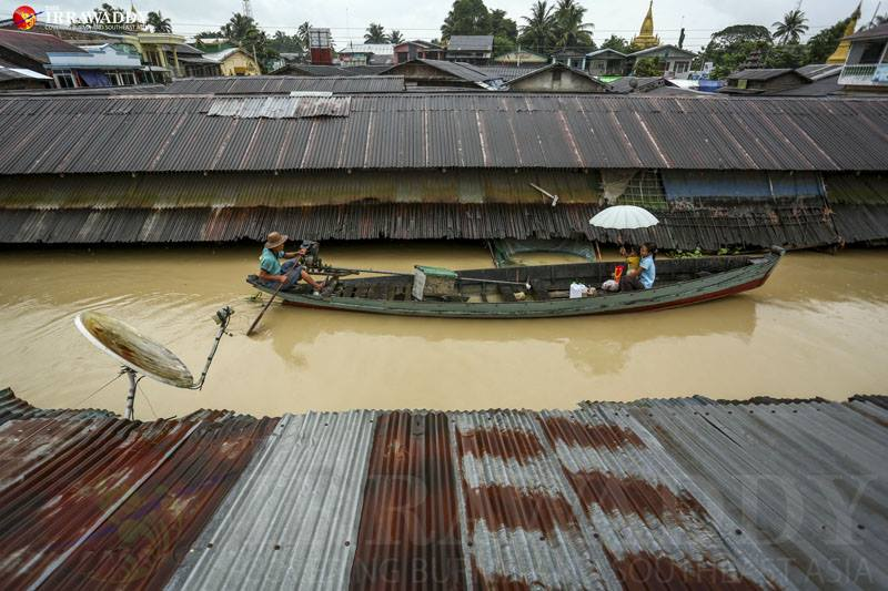 Locals travel by boat in Nyaungdon Township, Irrawaddy Division in September after flood waters inundated their homes. Photo by Thaw Hein Htet / The Irrawaddy