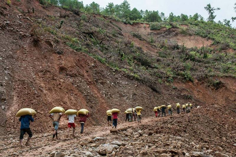 Locals carry relief supplies on the Gangaw-Hakha road near Chin State's Lan Thoke village on Aug. 28, 2015 after heavy flooding and landslides across the state. Photo by Sai Zaw / The Irrawaddy