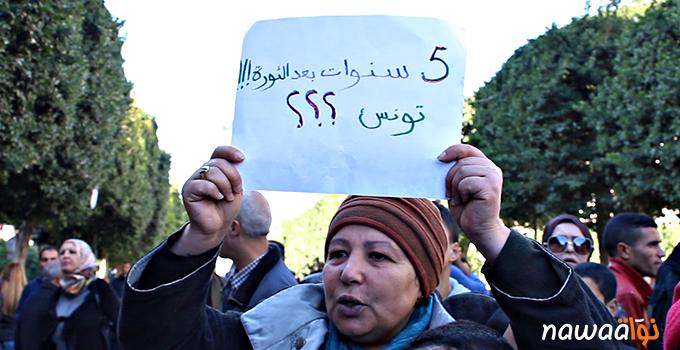 Een Tunesische demonstrante houdt een bord omhoog met de tekst: Vijf jaar na de revolutie!!! Tunesië??? Foto: Nawaat