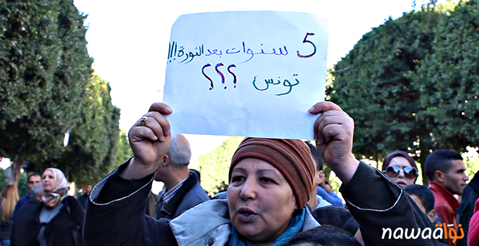 A Tunisian protester holding up a sign which reads: Five years after the revolution!!! Tunisia??? Photo credit: Nawaat