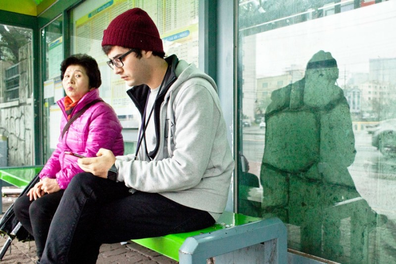 Ahmed Lababidi checks his phone waiting for the bus. Credit: Malte E. Kollenberg. Used with PRI's permission