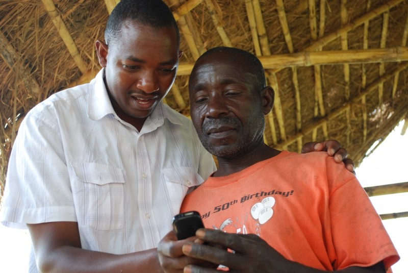 A trainer showing a farmer how to use the SMS Platform. photo Coutersy of WeFarm