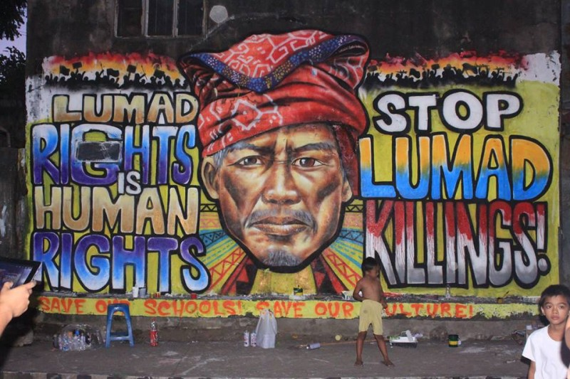 Un muro spoglio trasformato in un murales per sensibilizzare l'appello dei gruppi per i diritti umani che chiede di fermare la militarizzazione delle scuole Lumad. I Lumad sono una popolazione indigena a Mindanao, che si trova nella parte meridionale delle Filippine. Foto dalla pagina Facebook di Sim Tolentino