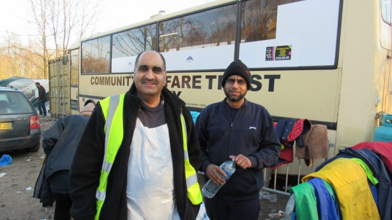 Ghafoor Hussain and his brother Fazel stand outside Ghafoor's bus-turned-mobile kitchen. They're supplying 3,000 hot meals a day, and 10,000 cups of tea. Credit: Adeline Sire. Used with PRI's permission