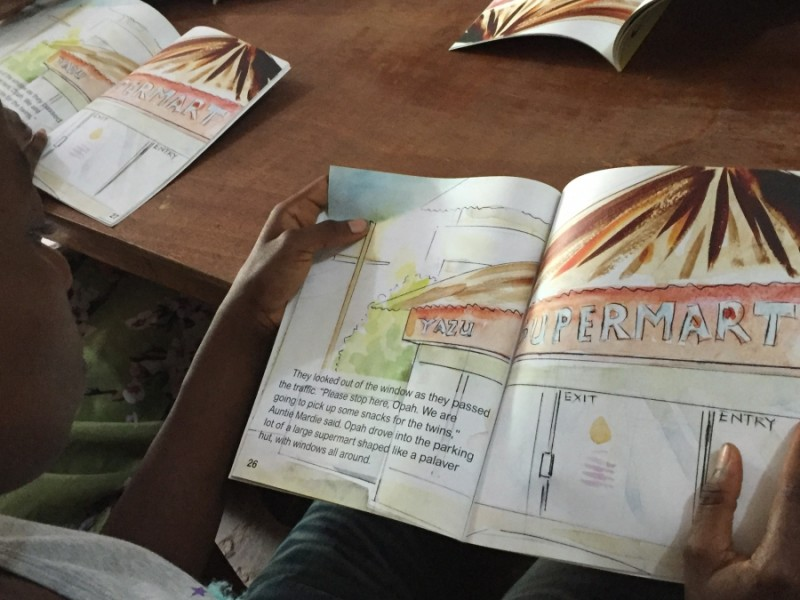 "Children read ""Gbagba,"" a book by Liberian author Robtel Neajai Pailey about corruption. Credit: Prue Clarke. Used with PRI's permission"
