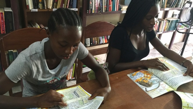 "Girls like Miatta (left)come to storytime at One Moore Bookstore in Monrovia. Owner Wayetu Moore (right) also publishes books like the one they're reading, ""Gbagba,"" a Liberian word that means ""corruption."" Credit: Prue Clarke. Used with PRI's permission"