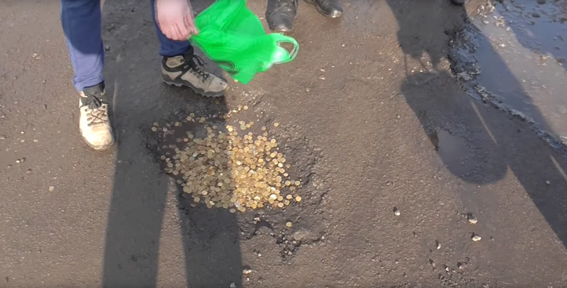 Russians bury their kopecks in potholes in a public protest against bad roads. Image: Alexander Rebrishchev / YouTube