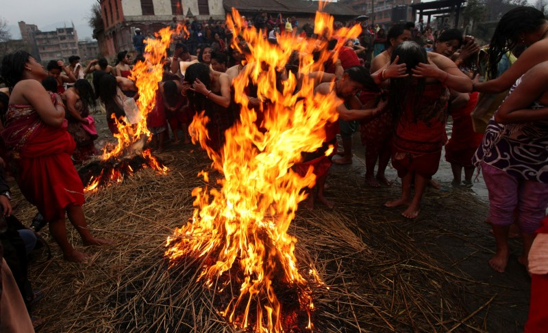 Nepalese Hindu women warm themelves after taking holy dips at the Hanumante River during Madhav Narayan festival in Bhaktapur, Nepal. Image by Sunil Sharma. Used with permission.