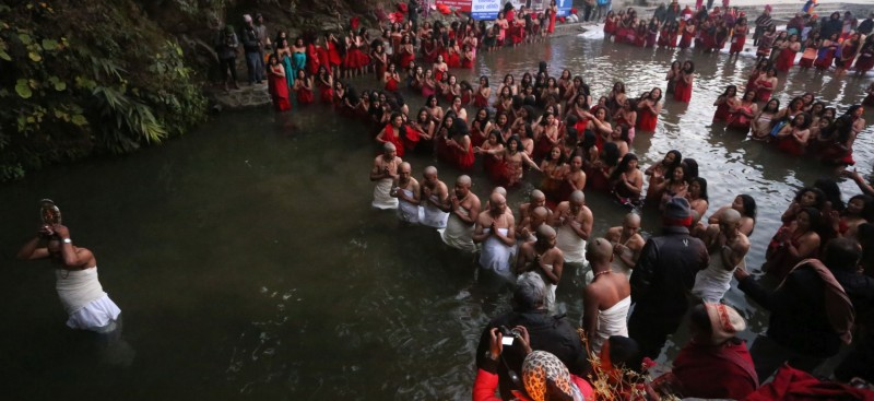 Nepalese Hindu devotees offer prayers before taking holy dips at Sali Nadi (River) during Madhav Narayan festival in Sankhu, Nepal. Nepalese Hindu women observe a fast and pray to Goddess Swasthani and God Madhav Narayan for longevity of their husbands and family prosperity during the month-long festival. Image by Sunil Sharma. Used with permission.