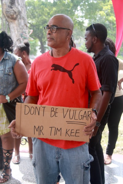 A male protestor holds a placard at the demonstration.