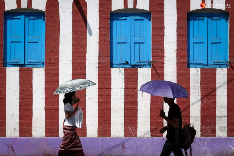 Yangon residents carry umbrella as protection from the heat of the sun. Photo by Hein Htet / The Irrawaddy