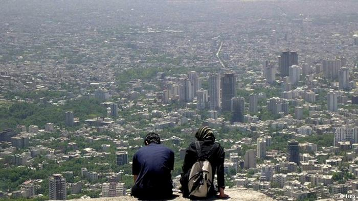A young couple sit atop a hill overlooking Tehran. Image from ICHRI.