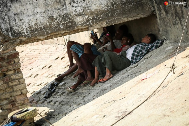 Yangon residents find a shade to rest. Photo by Hein Htet / The Irrawaddy