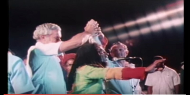 Screenshot of a YouTube video of the One Love Peace Concert, held in Jamaica on April 22, 1978. The concert was aimed at quelling the political violence of the election season; Bob Marley brought the leaders of the opposing political parties -- Michael Manley (PNP) and Edward Seaga (JLP) -- up on stage and joined their hands together in a symbolic gesture of unity.