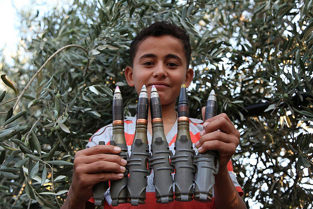 This 2012 photograph shows a Syrian boy holding anti-aircraft rounds up to the camera and smiling in the newly liberated town of Marayan in northern Syria. Photograph by Syria Freedom, shared on flickr and used under (CC BY 2.0