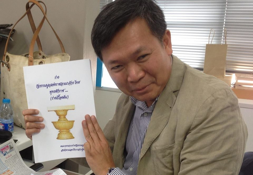 Pravit Rojanaphruk holding a copy of the draft constitution which some critics believe will reinforce military rule in Thailand. Pravit is seen flashing the three-finger sign which is also a symbol of protest used by pro-democracy forces in Thailand. Source: Facebook