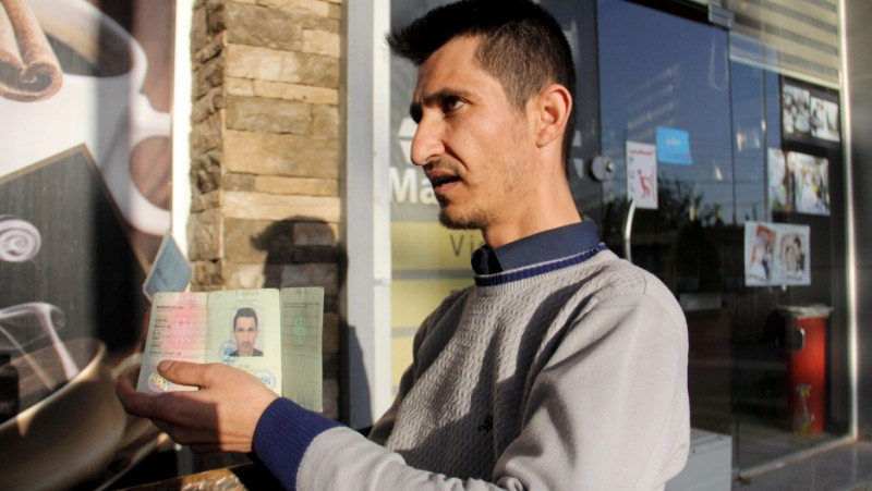 Dana Maghdeed Aziz holds up the identification issued to him by the Germany government. Credit: Rebecca Collard