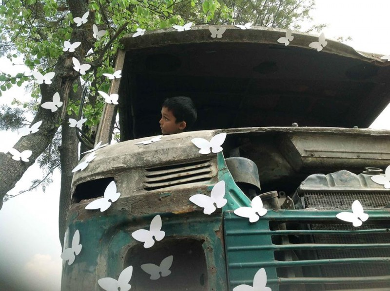 A boy looks on from an old abandoned vehicle installed with white butterflies. Image from the Facebook page of the White Butterfly project. Used with permission.