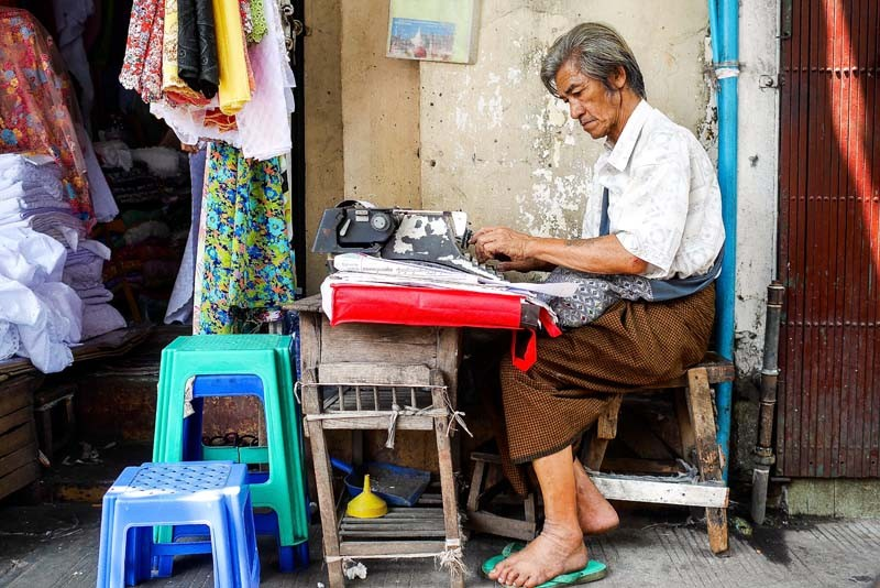 On downtown Yangon's Pansodan Street, a typist fills out legal documents from his sidewalk station. (Photo and caption: Tin Htet Paing / The Irrawaddy)