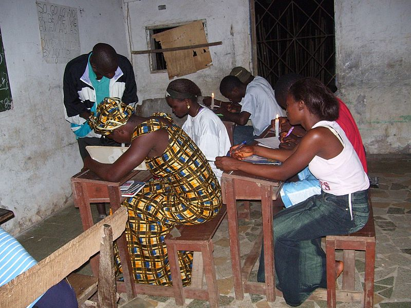 Students in Bong County, Liberia, study by candlelight. These students missed school during Liberia's civil war. Public Domain photo by United States Agency for International Development (USAID).