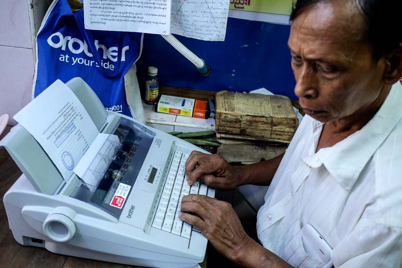 A man works on a document using an electric typewriter inside a downtown Yangon shop. While typists traditionally station themselves outdoors near courts and government offices, small indoor shops are opening in the vicinity, featuring more modern typewriters, as well as copiers and computers. (Photo and caption: Tin Htet Paing / The Irrawaddy)