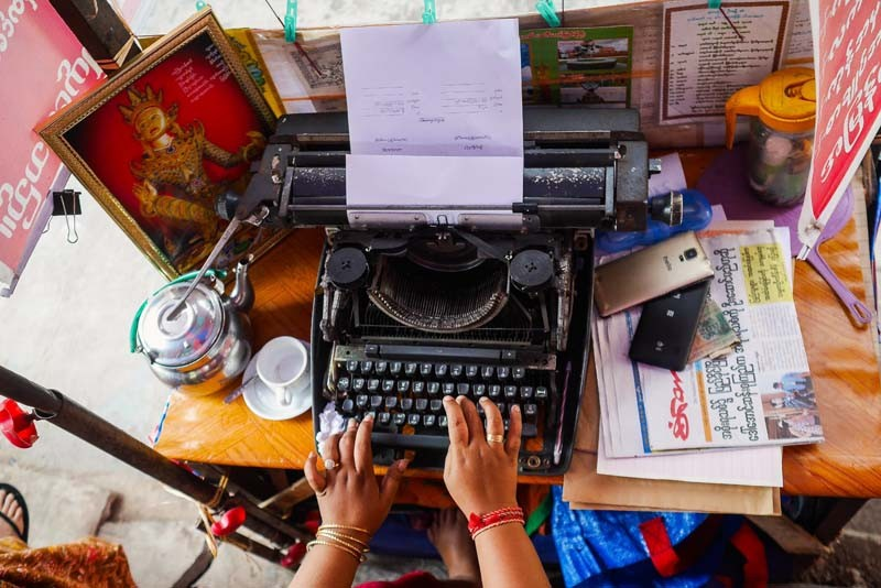 A female typist works on a document from her kiosk on lower Maha Bandoola Park Road. Like an increasing number of typists in Yangon, she relies on a typewriter professionally, but for personal purposes, she uses a smartphone. (Photo and caption: Tin Htet Paing / The Irrawaddy)