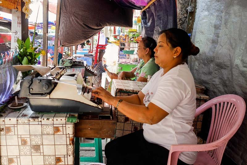 Female typists at work. While it is perceived as a field dominated by older men, The Irrawaddy found both men and women of varying ages typing up documents in streetside booths. (Photo and caption: Tin Htet Paing / The Irrawaddy)