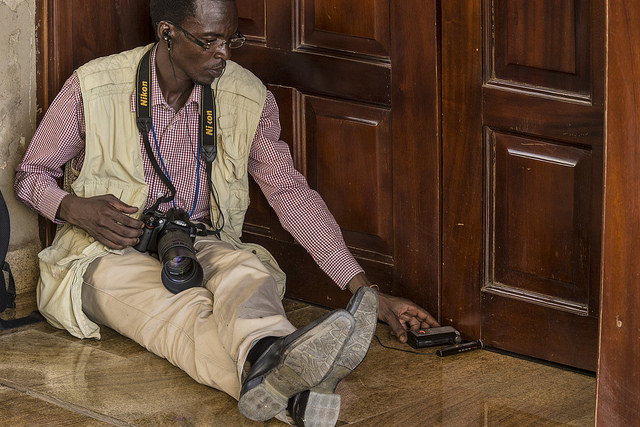 A South Sudanese journalist gathering news through the door at the State House during the swearing in of First Vice President Riek Machar on April 26, 2015. Only a few journalists were allowed to enter the hall. Photo released under Creative Commons by the United Nations Advance Mission in the Sudan (UNAMIS).