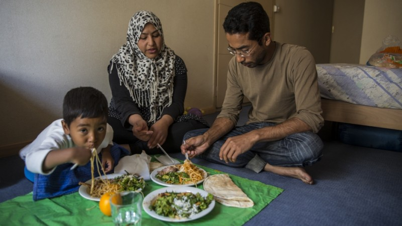 Ali Jaffari and his wife, Wajiha, and son Shayan, 4, eat dinner in their room while their other son naps. Together they traveled from Afghanistan to Greece, hoping to make their way to Germany. Now they are stuck in Greece. Credit: Jodi Hilton/Pulitzer Center on Crisis Reporting. Used with permission.