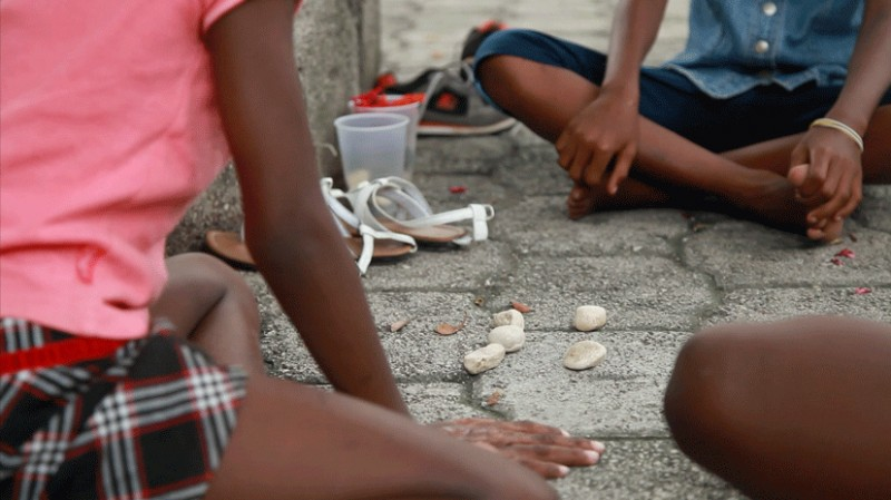 """14 million Child Marriages [globally]...but you've got to play the cards you're dealt."" Photo of stone games in Port-au-Prince, Haiti, by Thinking Development, which supports the work of www.girlsnotbrides.org in trying to put an end to Child Marriage. Image used under a CC BY 2.0 license."