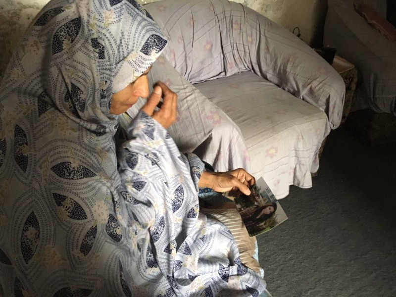 Kaneez Bibi looks at a photo of her missing daugher Zeenat Shahzadi. Photo by BBC reporter Saba Eitizaz, who first broke the story.